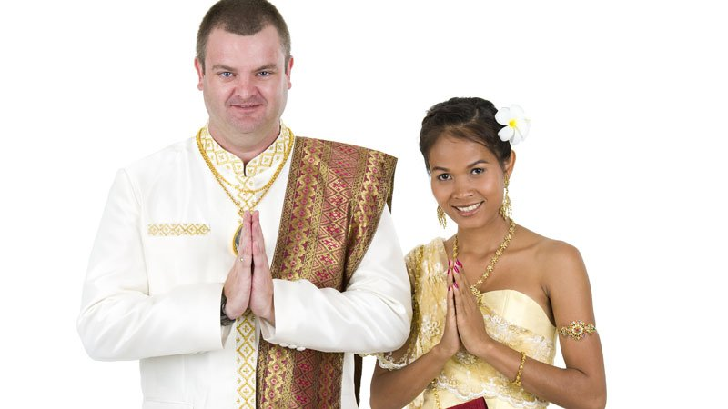 Western guy and Thai girl in traditional clothes