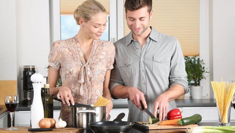 blonde-girl-cooking-pasta-with-her-partner