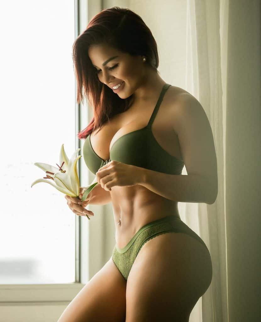 Dolly Castro in green bikini holding a flower
